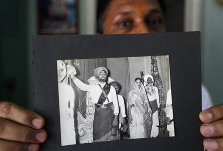 Head teacher A.R. Goswami shows an old photograph of Narendra Modi (2nd L), prime ministerial candidate for Bharatiya Janata Party (BJP), taking part in a play at a school in Vadnagar in Gujarat March 26, 2014. REUTERS/Amit Dave