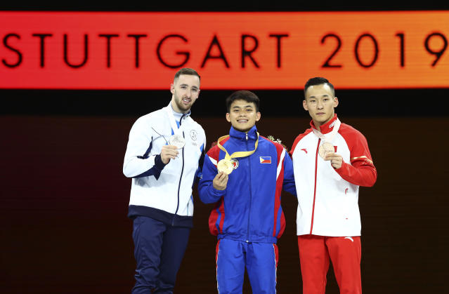 Carlos Edriel Yulo of the Philippines, center and gold medal, Artem Dolgopyat of Israel, left and silver medal, and Xiao Ruoteng of China, right and bronze medal, show their medals during the award ceremony for the men's floor exercise during the apparatus finals at the Gymnastics World Championships in Stuttgart, Germany, Saturday, Oct. 12, 2019. (AP Photo/Matthias Schrader)