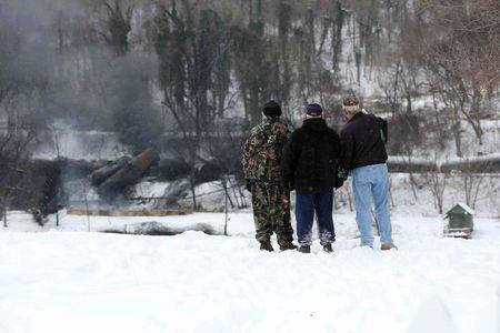 """From left, Anthony """"Buzz"""" Fish, 71, Lewis F. Fish 74, and Tom Graham, 73, all of Boomer, West Virginia, watch as a CSX Corp train continues to smolder a day after derailing in Mount Carbon, West Virginia, Tuesday, February 17, 2015. REUTERS/Marcus Constantino"""