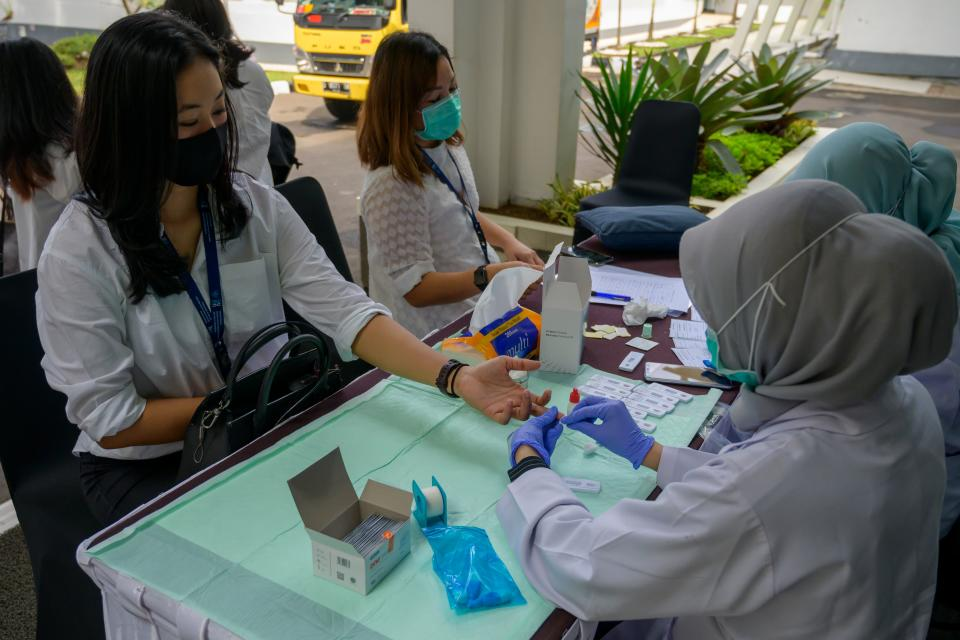 Health officials conduct a rapid test for visitors to the Bio Farma Pharmacy in Bandung, West Java on August 12, 2020. - Indonesia on August 11 launched human trials of a Chinese-made coronavirus vaccine with some 1,600 volunteers slated to take part in the six-month study. (Photo by Bay ISMOYO / AFP) / The erroneous mention[s] appearing in the metadata of this photo by Bay ISMOYO has been modified in AFP systems in the following manner: adds [which will produce the vaccine early next year with a production capacity of 250 million vaccines a year]. Please immediately remove the erroneous mention[s] from all your online services and delete it (them) from your servers. If you have been authorized by AFP to distribute it (them) to third parties, please ensure that the same actions are carried out by them. Failure to promptly comply with these instructions will entail liability on your part for any continued or post notification usage. Therefore we thank you very much for all your attention and prompt action. We are sorry for the inconvenience this notification may cause and remain at your disposal for any further information you may require. (Photo by BAY ISMOYO/AFP via Getty Images)