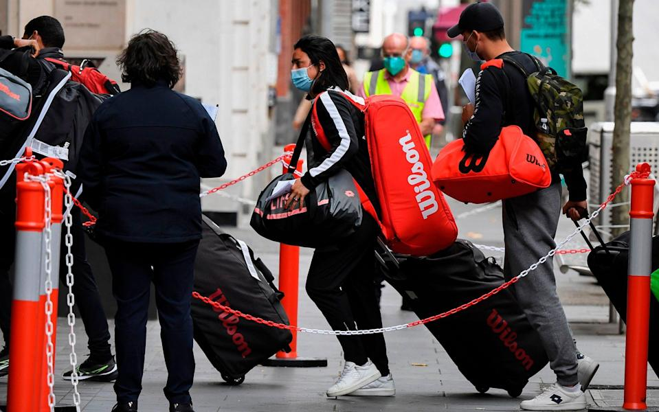 Tennis players, coaches and officials arrived at a hotel in Melbourne on Friday, before quarantining for two weeks ahead of the Australian Open - WILLIAM WEST/AFP