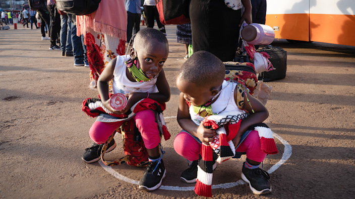Children in face masks crouch in white circles put at bus stations to ensure social distancing in Kigali, Rwanda -4 May 2020