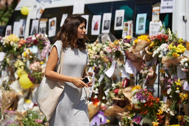 A woman views tributes left to victims of the Grenfell Tower blaze: AFP/Getty Images