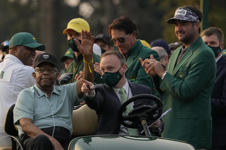 Lee Elder waves as he arrives for the ceremonial first tee shots before the first round of the Masters golf tournament on Thursday, April 8, 2021, in Augusta, Ga. Standing at right is Phil Mickelson and Bubba Watson. (AP Photo/Gregory Bull)