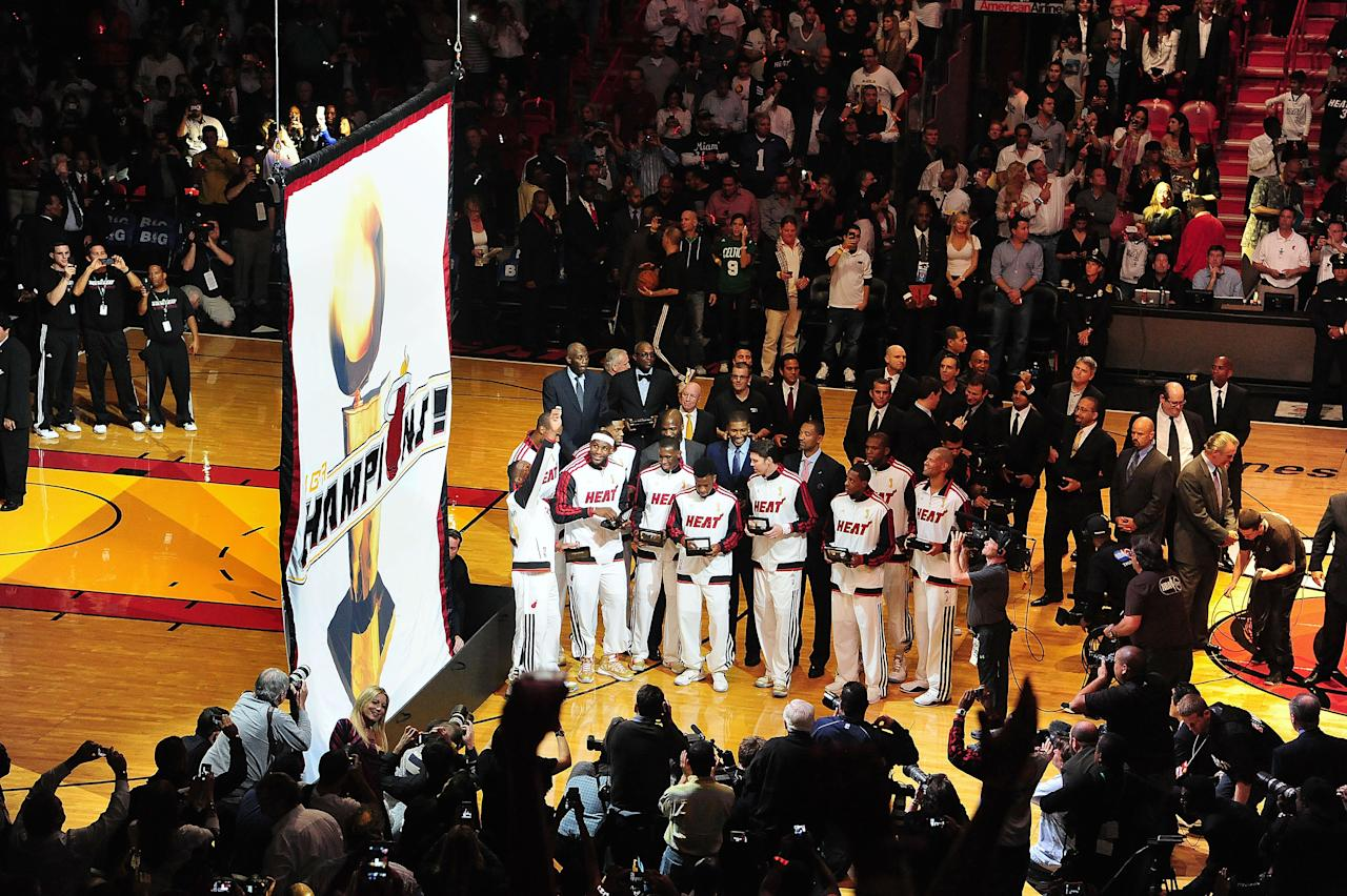 MIAMI, FL - OCTOBER 30: The Miami Heat watch as their 2012 NBA Championship banner is raised during a ceremony prior to the game against the Boston Celtics on October 30, 2012 at American Airlines Arena in Miami, Florida. NOTE TO USER: User expressly acknowledges and agrees that, by downloading and/or using this Photograph, user is consenting to the terms and conditions of the Getty Images License Agreement. Mandatory Copyright Notice: Copyright 2012 NBAE (Photo by Garrett W. Ellwood/NBAE via Getty Images)
