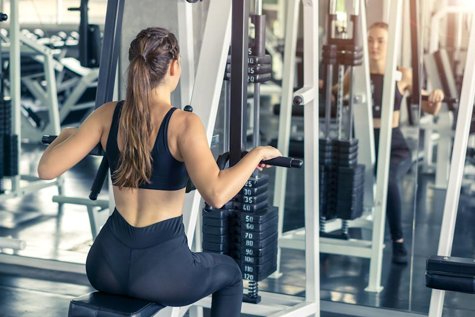 A young woman flexing muscles in fitness gym centre.