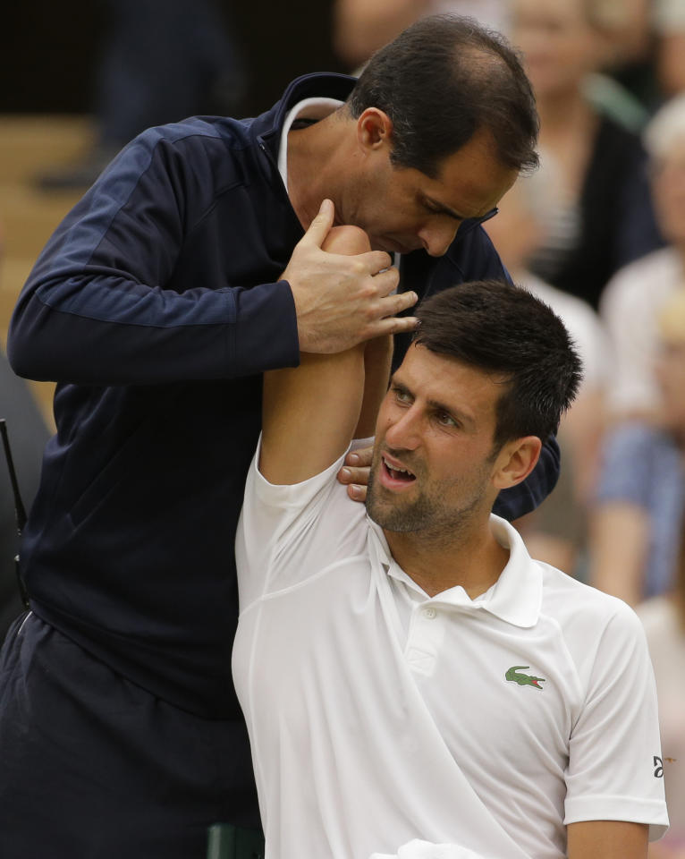 FILE - This is a Tuesday, July 11, 2017 file photo of Serbia's Novak Djokovic as he receives treatment from a trainer during a break in his Men's Singles Match against Adrian Mannarino of France on day eight at the Wimbledon Tennis Championships in London. Novak Djokovic will miss the rest of this season because of an injured right elbow. The 12-time major champion will skip the U.S. Open. That ends his streak of playing in 51 consecutive Grand Slam tournaments. (AP Photo/Alastair Grant/File)