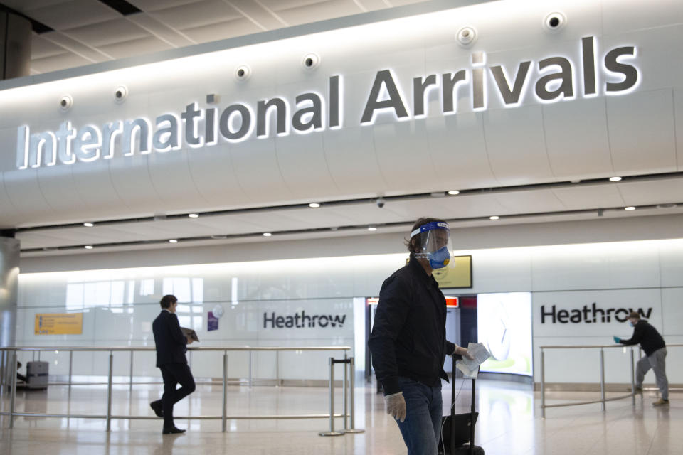 A passenger wearing a face shield and face mask arrives on the first day of new rules that people arriving in Britain from overseas will have to quarantine themselves for 14 days to help stop the spread of coronavirus, at Heathrow Airport in London, Monday, June 8, 2020. The British government has said that anyone caught not complying with the quarantine will face a fine. (AP Photo/Matt Dunham)