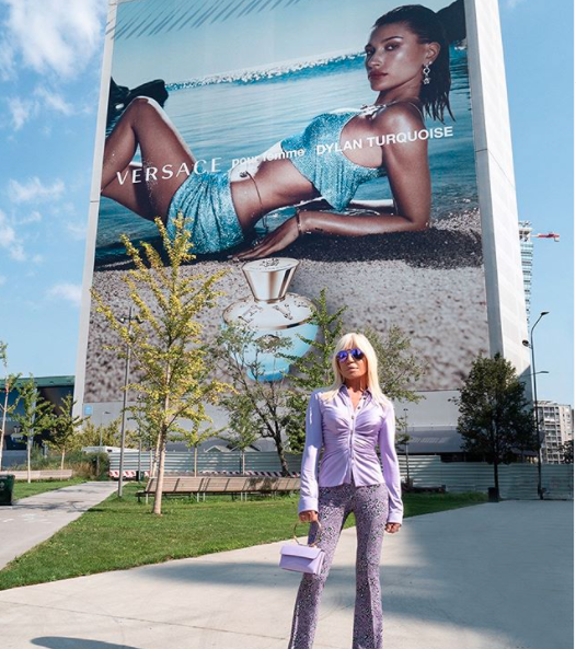 Donatella Versace posting in front of Hailey Bieber's Dylan Turquoise campaign