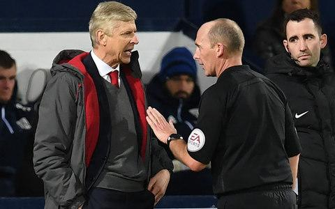 Arsenal's French manager Arsene Wenger (L) has words with English referee Mike Dean during the English Premier League football match between West Bromwich Albion and Arsenal at The Hawthorns stadium in West Bromwich, central England, on December 31, 2017 - Credit: AFP