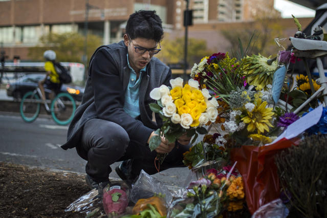 <p>Simon Rubin, 25, arranges flowers at a makeshift memorial to remember the victims of the recent truck attack near the crime scene on Thursday, Nov. 2, 2017, in New York. (Photo: Andres Kudacki/AP) </p>