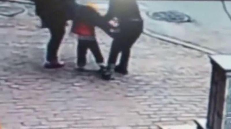 The hooded man can be seen snatching at the toddler's right hand. Source: TV Soho