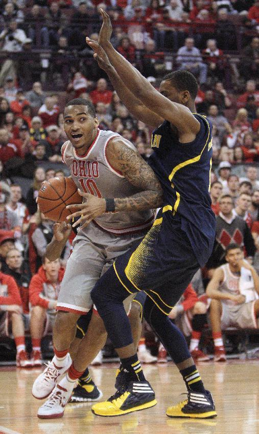 Ohio State's LaQuinton Ross, left, drives the baseline against Michigan's Glenn Robinson during the second half of an NCAA college basketball game Tuesday, Feb. 11, 2014, in Columbus, Ohio. Michigan defeated Ohio State 70-60. (AP Photo/Jay LaPrete)