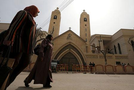 Women pass by the Coptic church that was bombed on Sunday in Tanta