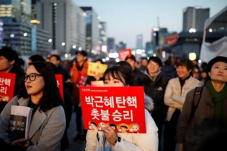 People attend a rally calling for impeached President Park Geun-hye's arrest in central Seoul