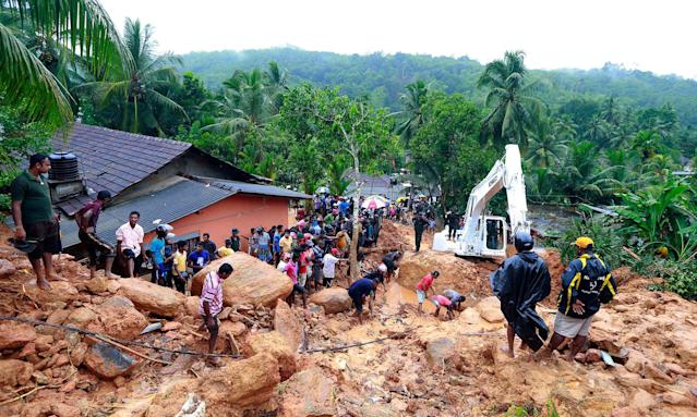 <p>Sri Lankans watch military rescue efforts at the site of a landslide at Bellana village in Kalutara district, Sri Lanka, Friday, May 26, 2017. (AP Photo/Eranga Jayawardena) </p>