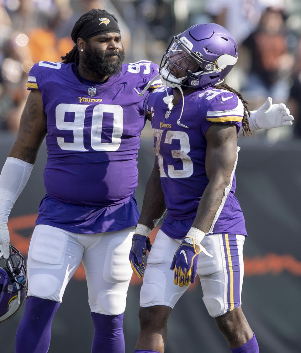Minnesota Vikings defensive tackle Sheldon Richardson (90) pats Dalvin Cook (33) on the back after Cook fumbled the ball in overtime of an NFL football game against the Cincinnati Bengals, Sunday, Sept. 12, 2021, in Cincinnati. (Carlos Gonzalez/Star Tribune via AP)