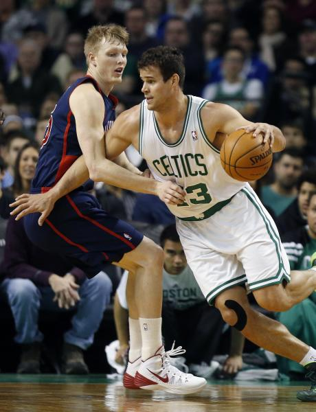 Boston Celtics' Kris Humphries, right, drives past Detroit Pistons' Kyle Singler, left, in the first quarter of an NBA basketball game in Boston, Sunday, March 9, 2014. (AP Photo/Michael Dwyer)