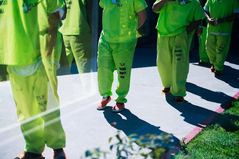 Men wearing neon-colored jail clothes signifying immigration detainees walk to pick up their lunches at the Theo Lacy Facility, a county jail which houses convicted criminals as well as immigration detainees, March 14, 2017 in Orange, California, about 32 miles (52km) southeast of Los Angeles.US President Donald Trumps first budget provides more than USD 4.5 billion in new spending to fight illegal immigration by adding immigration and border enforcement agents, prosecutors and judges, as well as building a wall on the border with Mexico. / AFP PHOTO / Robyn Beck (Photo credit should read ROBYN BECK/AFP/Getty Images)