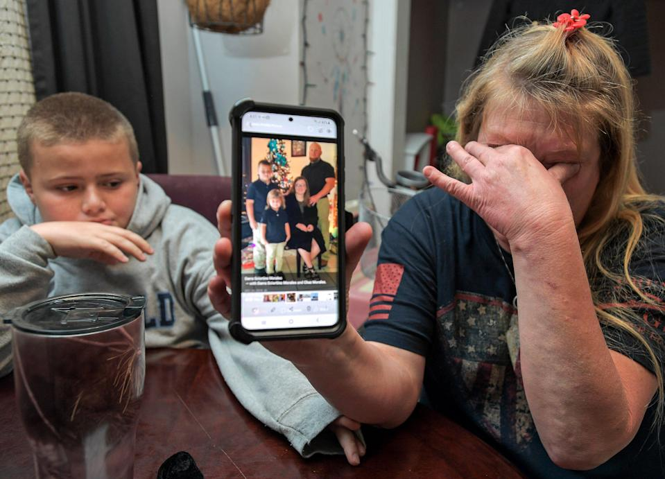 Darra Ann Morales, right, shows a photo of her son Chaz and his family on her phone as Chaz Jr. comforts his grandmother at their home in Slidell, La., on April 14.