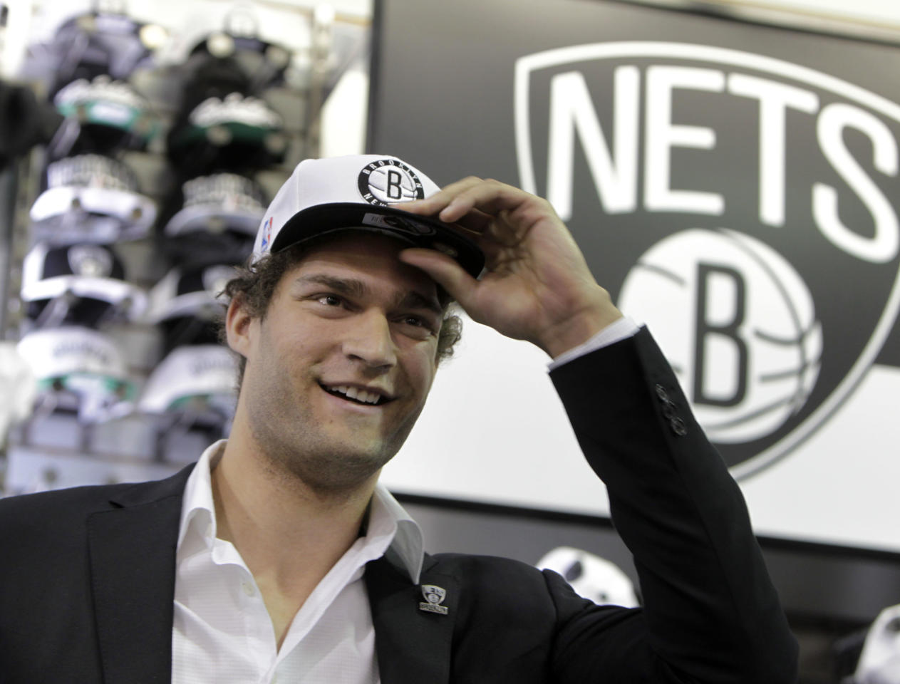 Brooklyn Nets basketball player Brook Lopez tries on a hat with the new Nets' logo during a news conference to unveil the new logos in the Brooklyn borough of New York, Monday, April 30, 2012. The Nets will be moving from New Jersey to the new Barclays Center in Brooklyn, New York for the 2012-2013 NBA basketball season. (AP Photo/Seth Wenig)