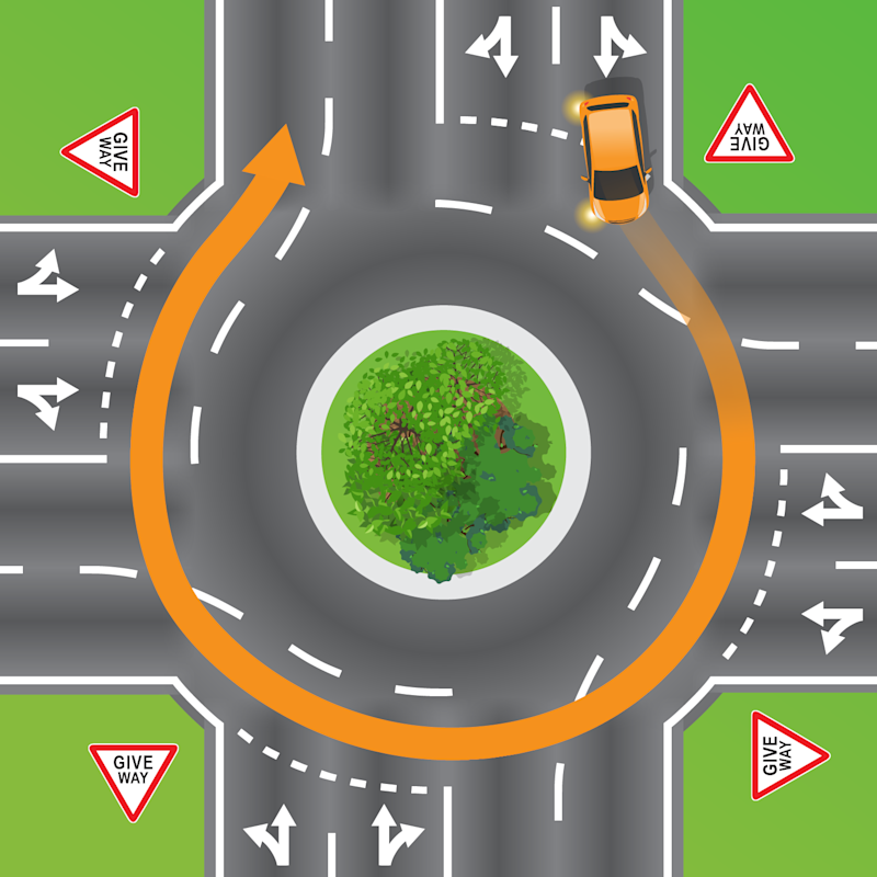 An orange car is pictured at a four-exit roundabout.