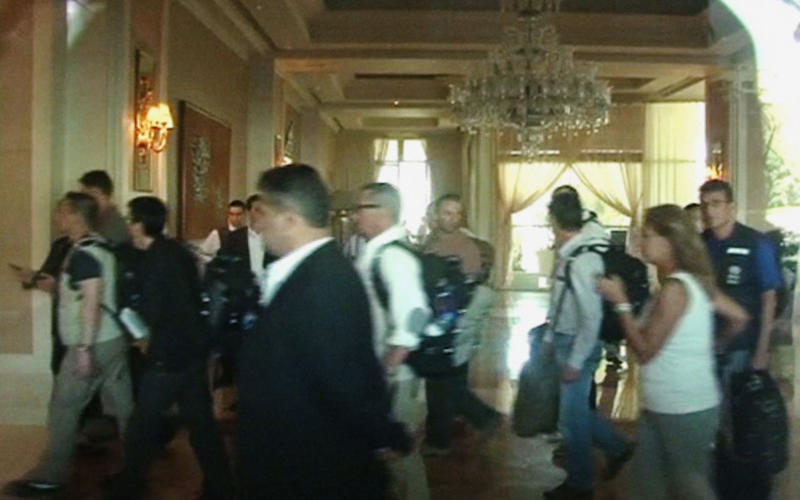 In this image made from video, U.N. weapon inspectors, seen through window, walk through the hotel lobby upon their arrival at a hotel in Damascus, Syria, Sunday, Aug. 18, 2013. A team of U.N. weapons inspectors arrived in Damascus on Sunday for a long-delayed mission to investigate the alleged use of chemical arms in Syria's civil war. (AP Photo/AP Video)