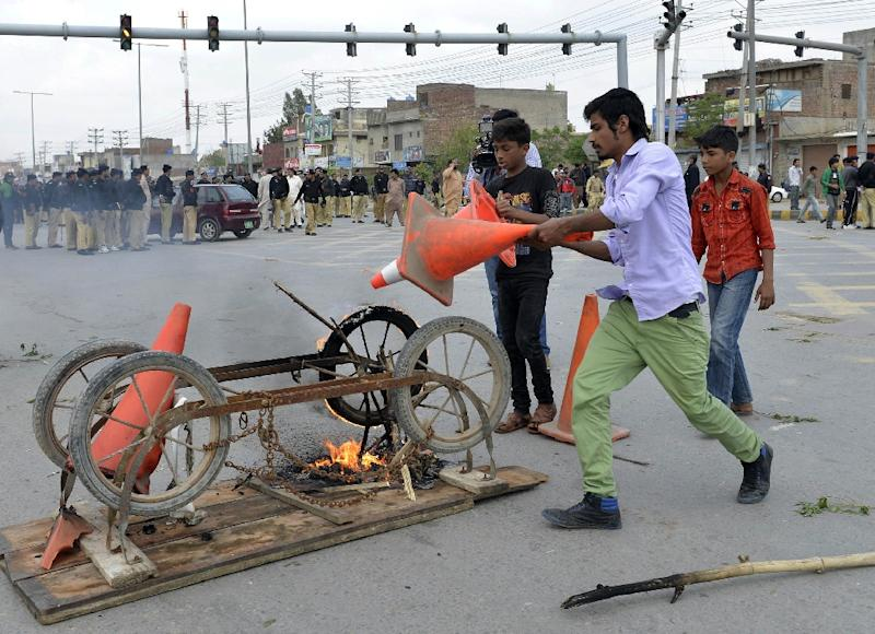 Pakistani Christians set fire to a cart during a protest following suicide bomb attacks on churches in Lahore, on March 15, 2015 (AFP Photo/Arif Ali)