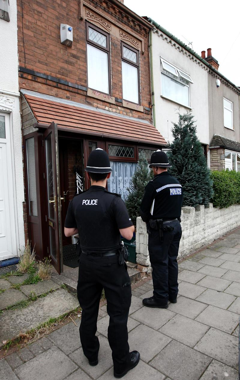 Police guard a house in Asquith Rd, Ward End, Birmingham, England  following the arrest of six men in Birmingham as part of a large intelligence-led counter-terrorism operation Monday Sept.  19, 2011. The men were detained at or near their homes overnight on suspicion of the commission, preparation or instigation of an act of terrorism in Britain. A spokeswoman for West Midlands Police said the men, aged between 25 and 32, were taken into custody by unarmed officers in the Moseley, Sparkbrook, Sparkhill, Ward End and Balsall Heath areas of Birmingham. (AP Photo/David Jones/PA)