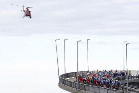 Cycling - UCI Road World Championships - Men Elite Road Race - Bergen, Norway - September 24, 2017 – Competitors cross a bridge while helicopter flies over the pelothon. NTB Scanpix/Cornelius Poppe via REUTERS