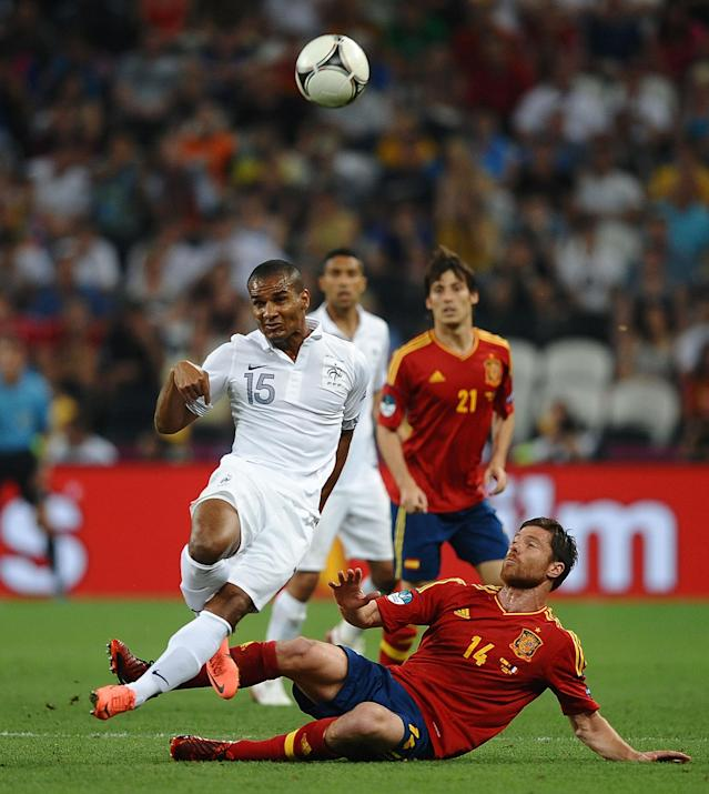 DONETSK, UKRAINE - JUNE 23: Xabi Alonso of Spain challenges Florent Malouda of France during the UEFA EURO 2012 quarter final match between Spain and France at Donbass Arena on June 23, 2012 in Donetsk, Ukraine. (Photo by Laurence Griffiths/Getty Images)