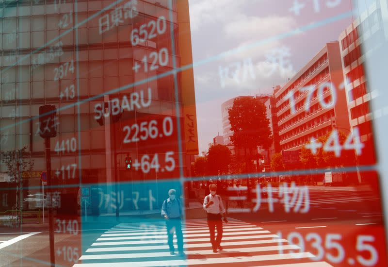 People wearing protective masks, following the coronavirus disease (COVID-19) outbreak, are reflected on a screen showing stock prices outside a brokerage in Tokyo