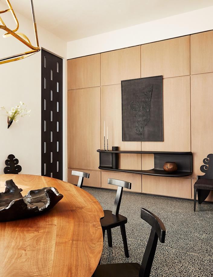 An artwork by Louise Nevelson hangs in the dining room. Joseph Walsh Table with Olavi Hänninen Chairs; Carol Egan wall-mounted Console.