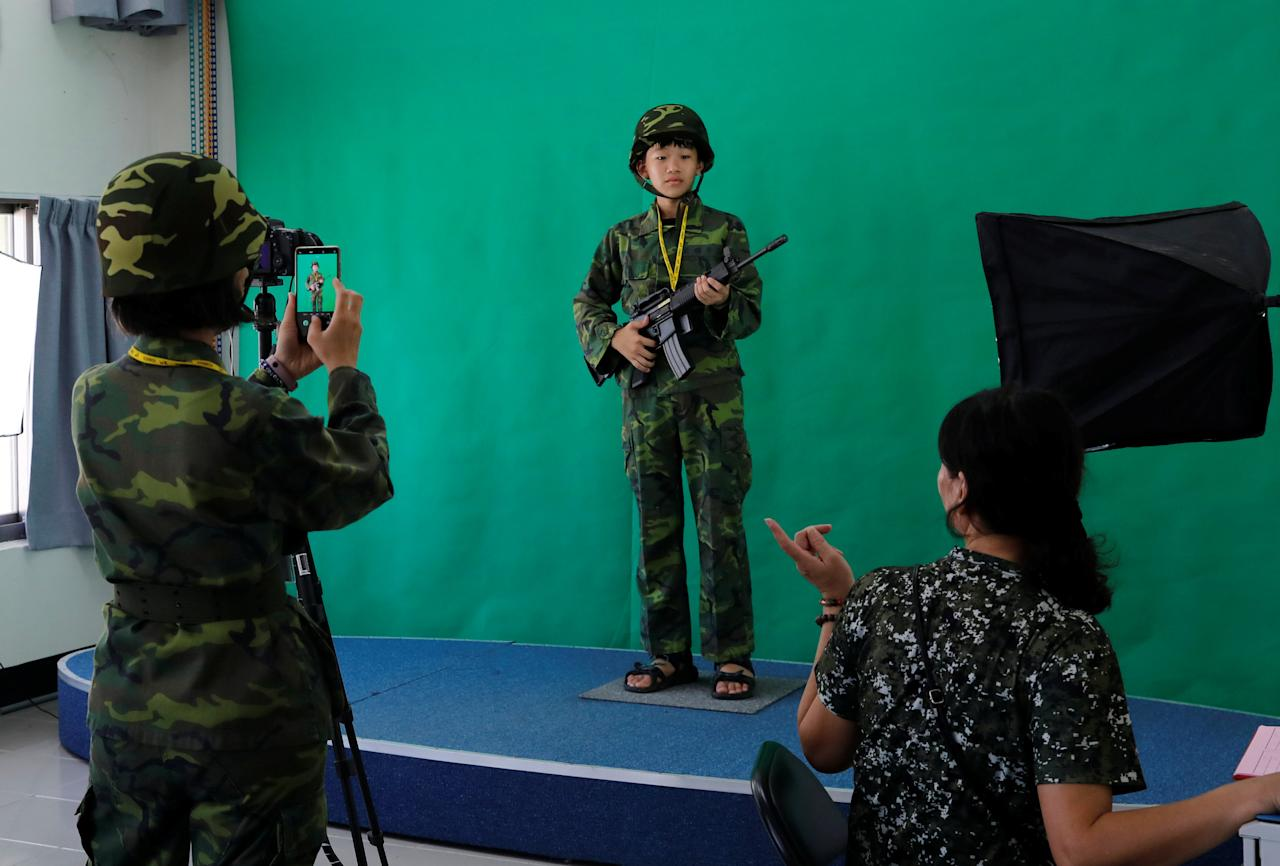 Tourists pose for a photo before taking part in an electronic shooting game simulating the 1958 attacks, ahead of the 60th anniversary of Second Taiwan Straits Crisis against China, on Lieyu island, Kinmen county, Taiwan August 20, 2018. REUTERS/Tyrone Siu