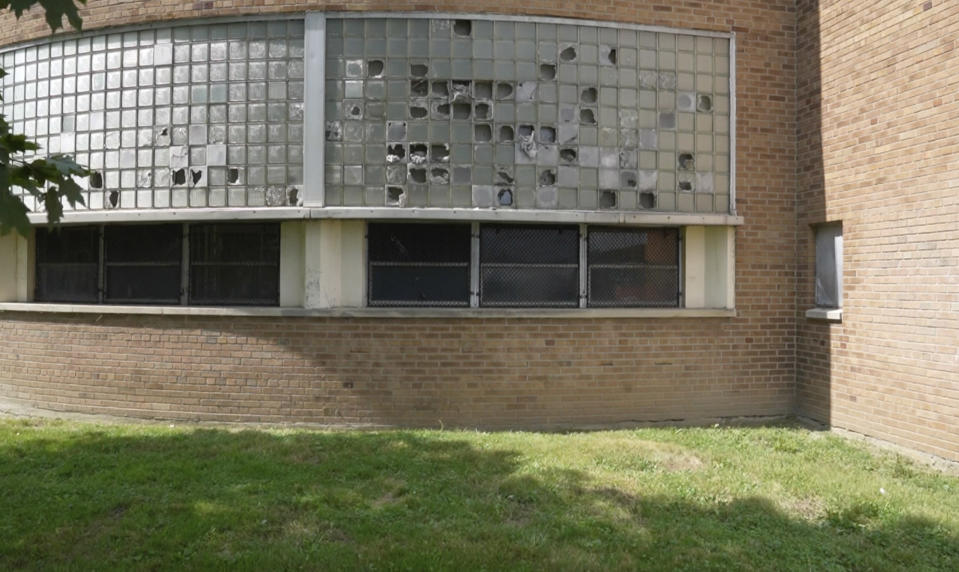 Broken windows are seen outside Cody High School in Detroit on Friday, Aug. 20, 2021. Like other school systems, Detroit is caught between the Biden administration's lofty aspirations and bleak realities. The district is using some of the government money to hire tutors, expand mental health services and cut class sizes. But at least half of its $1.3 billion windfall is being set aside to make long-neglected repairs. (AP Photo/Carlos Osorio)