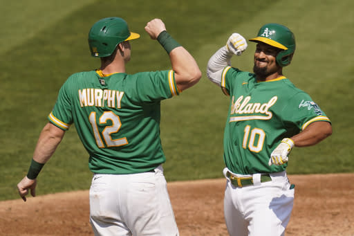 Oakland Athletics' Marcus Semien (10) celebrates after hitting a two-run home run that scored Sean Murphy (12) against the Chicago White Sox during the second inning of Game 2 of an American League wild-card baseball series Wednesday, Sept. 30, 2020, in Oakland, Calif. (AP Photo/Eric Risberg)