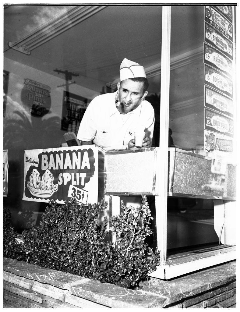 <p>A parlor worker looks out the very window that advertises 35-cent banana splits. Today, that price equals approximately $3.56.</p>