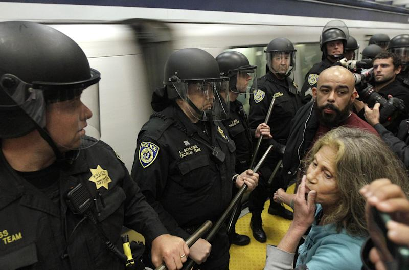 In this photo from Monday, Aug. 15, 2011, Bay Area Rapid Transit (BART) police officers block protesters from a train at the Civic Center station in San Francisco.   Rather than resort to another shutdown of subway cellular service to deter protesters, the San Francisco Bay Areaís transit agency closed down stations in the path of marchers, inconveniencing thousands of evening commuters. Bay Area Rapid Transit officials said they undertook the strategy to protect public safety on train platforms. (AP Photo/Jeff Chiu)