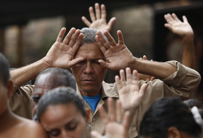 """<p>Venezuelan migrants pray before lunch at the """"Divina Providencia"""" migrant shelter run by the diocese of Cucuta, in Cucuta, Colombia, Feb. 23, 2018, on the border with Venezuela. The diocese offers an average of 1000 meals a day for the migrants. (Photo: Fernando Vergara/AP) </p>"""