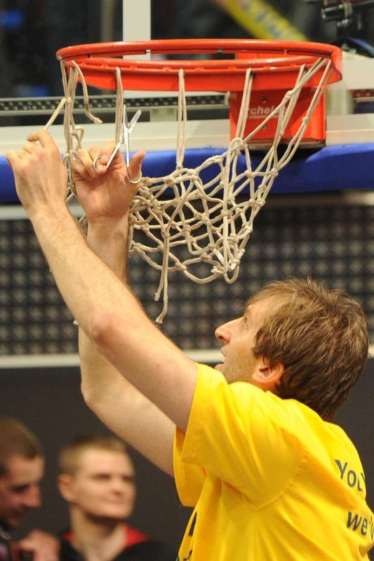 BC Khimki's Zoran Planinic cuts the net as he celebrates winning the Eurocup final basketball match between BC Khimki and Valencia in Khimki, outside Moscow on April 15, 2012. BC Khimki won 77-68. AFP PHOTO / KIRILL KUDRYAVTSEV