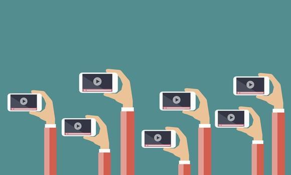 A bunch of cartoon hands holding up mobile phones that are on a video play screen.