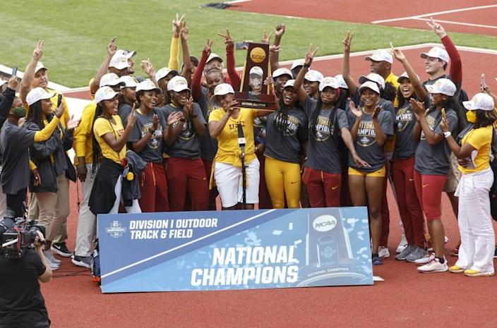 The USC women's track and field team accepts the team trophy after winning the NCAA championship Saturday in Eugene, Ore.