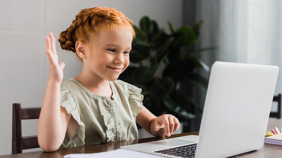 beautiful little girl with laptop making video call.
