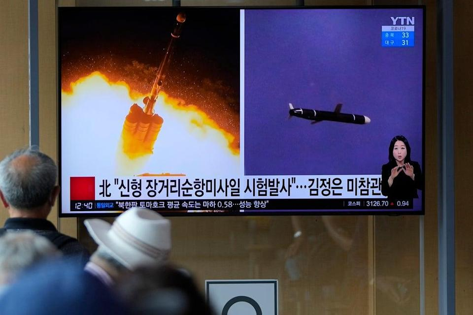People watch a TV screen showing a report about North Korea's long-range cruise missiles tests on Monday (AP)