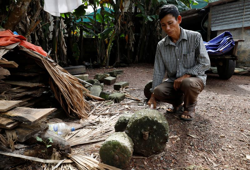 Nguyen Dinh Gia shows a barbell which was used by his son Nguyen Dinh Luong, a victim who was found dead in the back of British truck, at home in Ha Tinh province