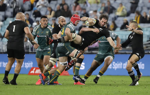 New Zealand's Sam Whitelock is tackled by Australia's Harry Wilson during the Bledisloe rugby test between the All Blacks and the Wallabies at Stadium Australia, Sydney, Australia, Saturday, Oct. 31, 2020. (AP Photo/Rick Rycroft)