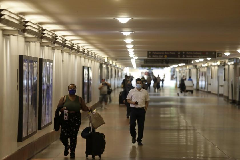 LOS ANGELES, CA - June 15, 2021 - Travelers still wear masks while arriving at Union Station on the first day that California reopened its economy in Los Angeles on June 15, 2021. California rescinded most mask rules for vaccinated people and ended capacity limitations on businesses and venues. Masks are still required at some places including airports, train stations and while traveling by bus. (Genaro Molina / Los Angeles Times)
