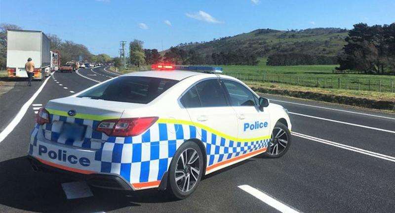 A police car is parked across one of the lanes of the Midland Highway where three people were killed in a horrific car crash.