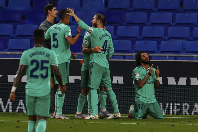 Real Madrid players celebrate their victory at the end of the Spanish La Liga soccer match against RCD Espanyol at the Cornella-El Prat stadium in Barcelona, Spain, Sunday, June 28, 2020. (AP Photo/Joan Monfort)