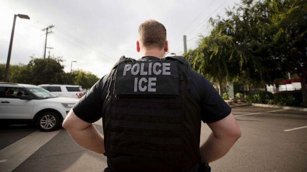 PHOTO: In this July 8, 2019, file photo, a U.S. Immigration and Customs Enforcement (ICE) officer looks on during an operation in Escondido, Calif.  (Gregory Bull/AP, FILE)